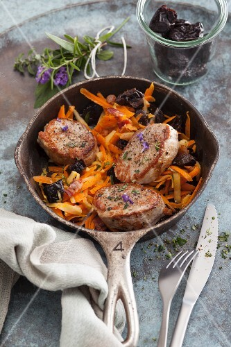 Fried pork medallions on a dried plum and carrot medley