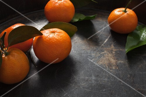 Five clementines with stems and leaves