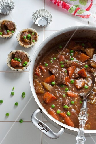 Hearty beef stew in a pot and in pastry cases