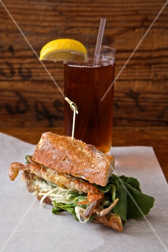A soft shell crab sandwich served with iced tea