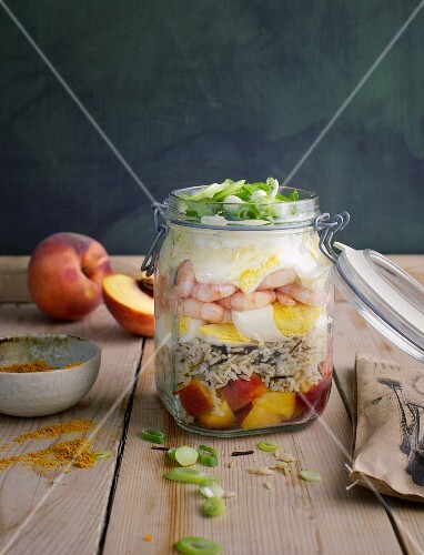 A layered salad with prawns, rice, peach and egg