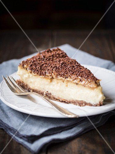 A slice of vegan millet cheesecake with date caramel on a dark surface