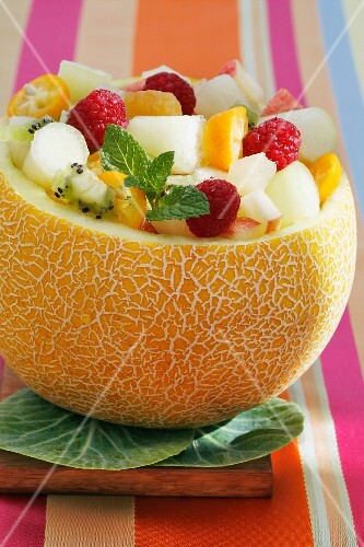 A melon filled with fruit salad