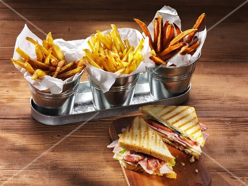 Three types of chips and a ham, cheese, tomato and lettuce sandwich on a rustic wooden table