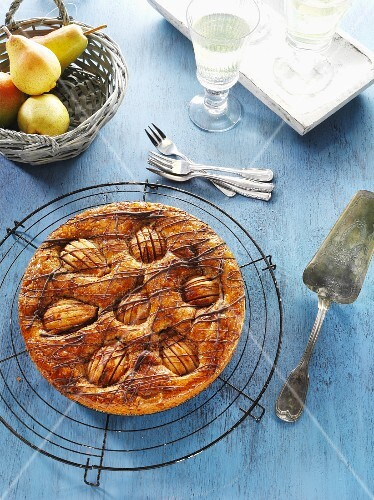 Ganzer Birnenkuchen auf Tortengitter auf blauem Holztisch