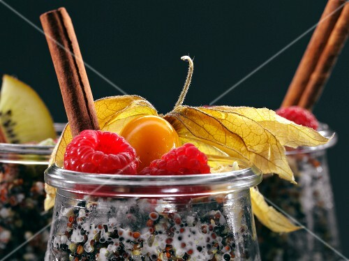Quinoa breakfasts with rasberries, cinnamon sticks and physalis in glasses