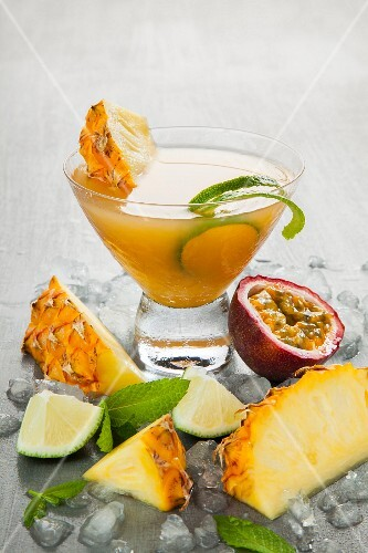 A cocktail made with pineapple, lime and passion fruit juice