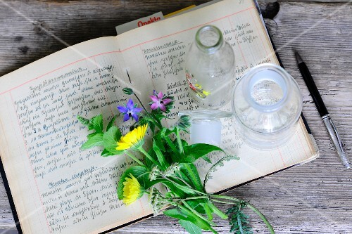 Wild flowers and apothecary bottle on open recipe book