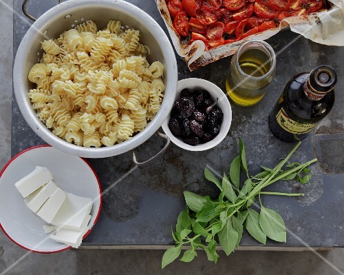 An arrangement of cooked pasta, olives, basil and olive oil