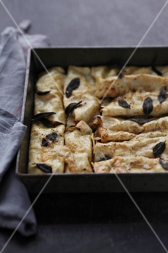 Gratinated pancake rolls filled with minced meat and sage