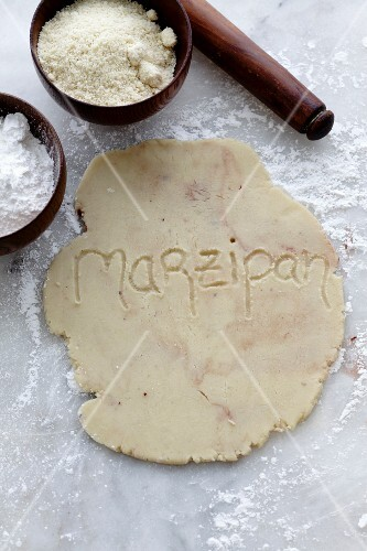 Rolled out, home-made marzipan on a marble surface with the word marzipan written on it