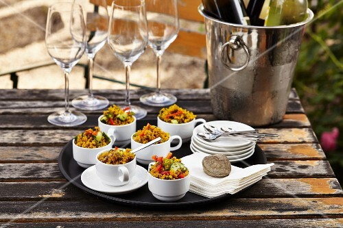 Couscous salad in coffee cups on a black tray