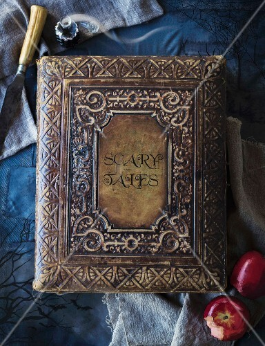 Antique, leather-bound book of fairy tales on blue surface as Halloween decoration