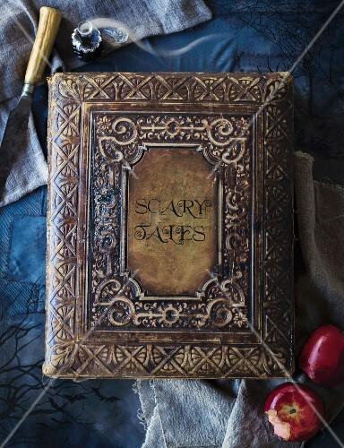 Antikes Märchenbuch mit Ledereinband auf blauem Untergrund als Halloweendekoration