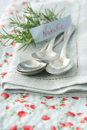 Silver spoons on napkin with name tag and sprig of rosemary