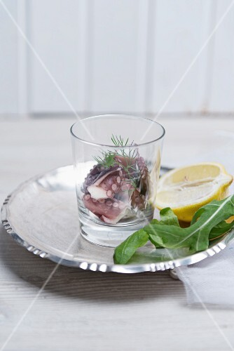 Squid with fresh dill in a glass on a metal plate with a rocket leaf and half a lemon