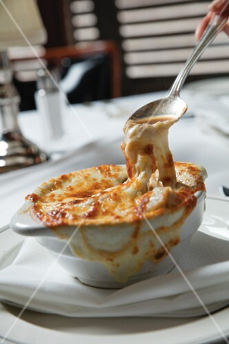 French onion soup being eaten in a restaurant