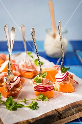 Papaya canapés with radishes, prosciutto and mint