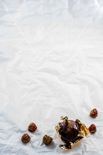 Raspberries dusted with gold powder and a fig wrapped in gold leaf