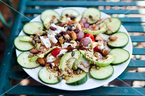 Cucumber salad with avocado, cashew nuts, seeds and olives
