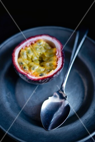 Half a passion fruit on a pewter plate with a silver spoon