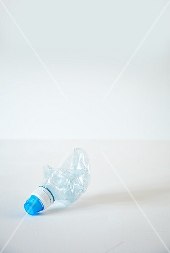 An empty squashed plastic water bottle