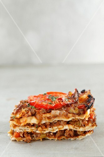 A portion of lasagne with minced meat and tomatoes