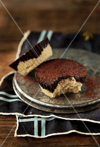 Two vegan chocolate coconut tartlets, one with a bite taken out
