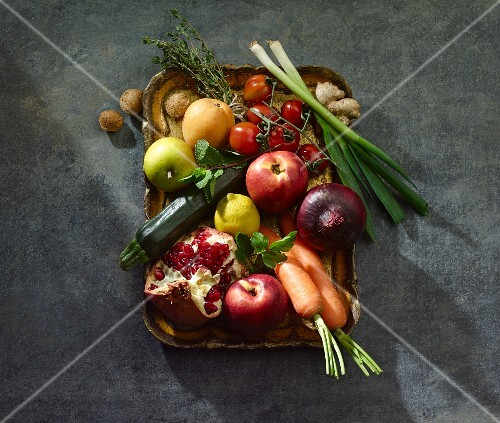 Various fruits and vegetables with ginger, herbs and almonds on a tray