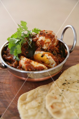 Boiled eggs with red masala and naan bread (India)