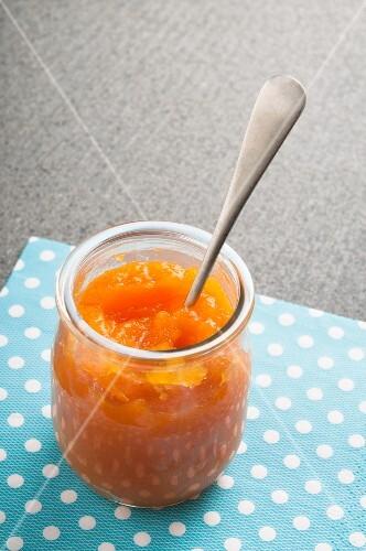 A jar of pumpkin and orange marmalade with a spoon