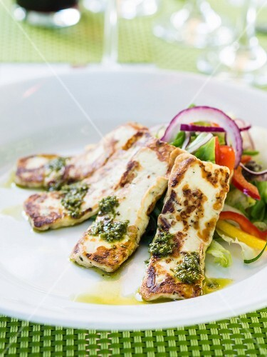 Grilled halloumi cheese served with pesto and salad