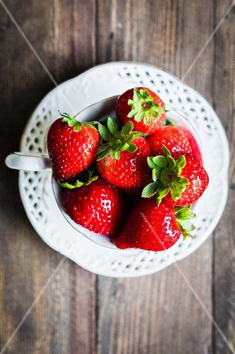 Fresh strawberries in a teacup on a wooden table