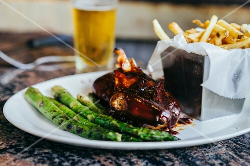 Barbecue chicken with green asparagus and French fries