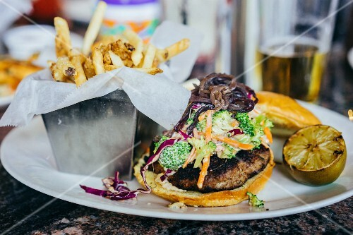 A burger with coleslaw and French fries