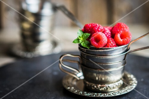Fresh raspberries in a stack of silver cups