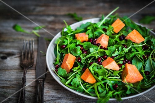 Fresh rocket and spinach salad with pumpkin and pomegranate seeds