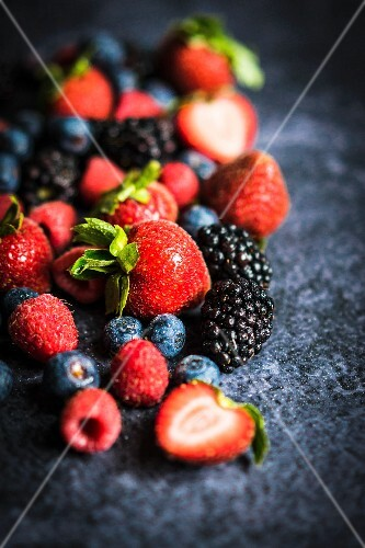 Various berries on a rustic black surface