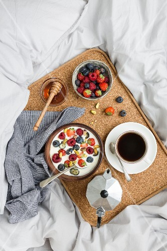 Coffee, berry yoghurt, honey and fresh berries on a breakfast tray