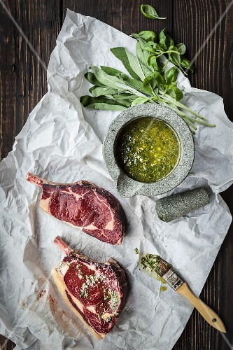 An arrangement of raw chops and a freshly ground herb marinade in a mortar