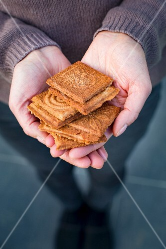Hands holding a stack of cinnamon waffles
