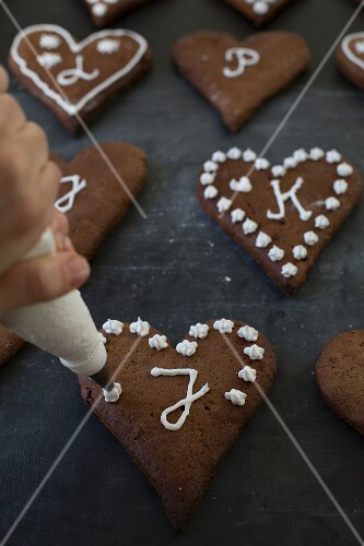 Gingerbread biscuits being decorated with icing