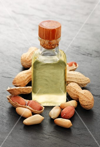 A bottle of peanut oil surrounded by peanuts