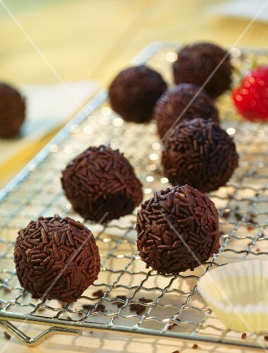 Rum truffles with chocolate sprinkles on a wire rack