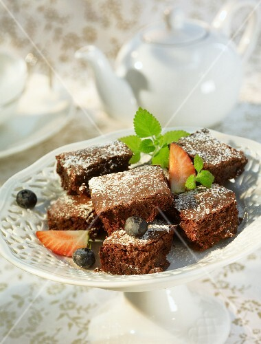 Pieces of chocolate cake with icing sugar and berries