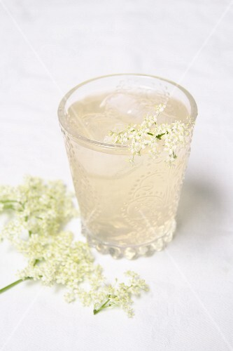 A glass of elderflower spritzer with ice cubes