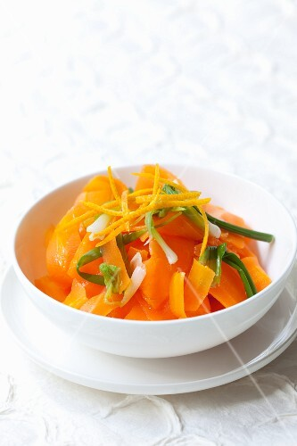 A salad made from cooked carrots with oranges and spring onions