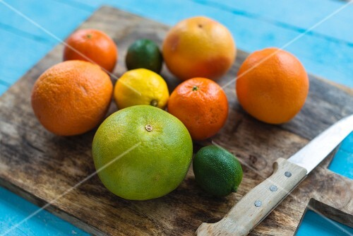 Various citrus fruits on a chopping board with a knife