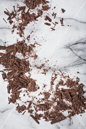 Grated dark chocolate on a marble surface