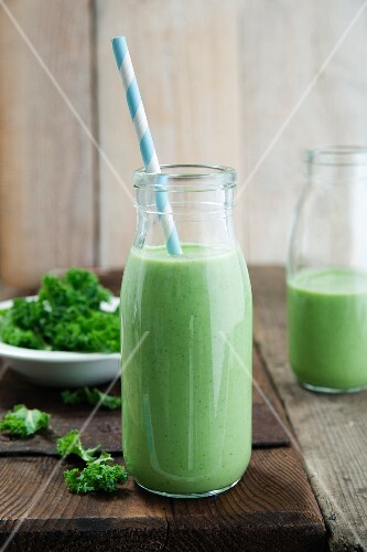 Kale and apple smoothie in a glass bottle with a straw